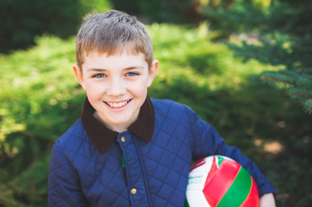 Boy smiling while holding a volleyball.