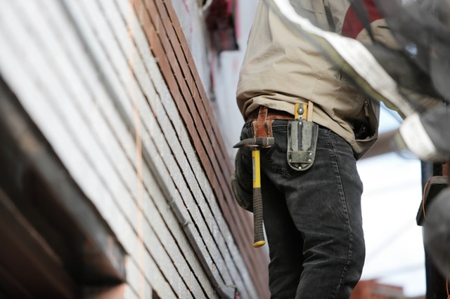 Man wearing tool belt. Standing by a side of a building.