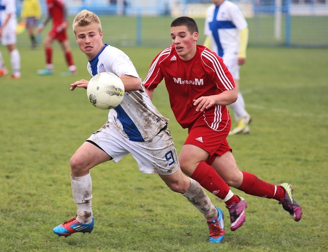 Two young men running playing soccer.