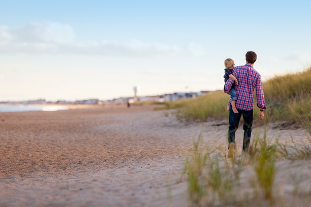Man carrying child walking on a beach.