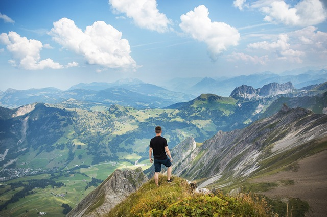 Man standing on mountain overlooking the valley.