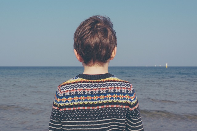 Boy standing on a beach staring at the ocean.