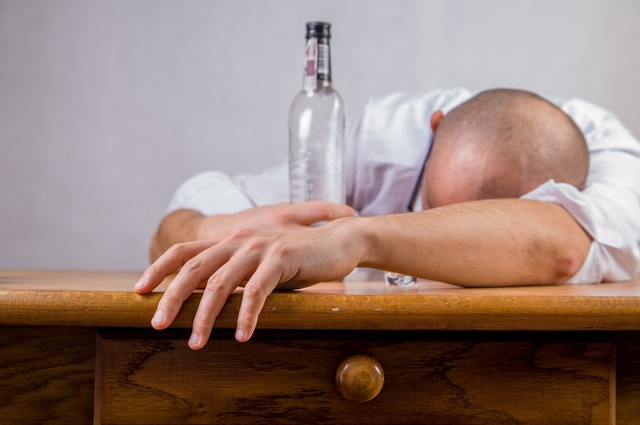 Man passed out on a table with an empty bottle.