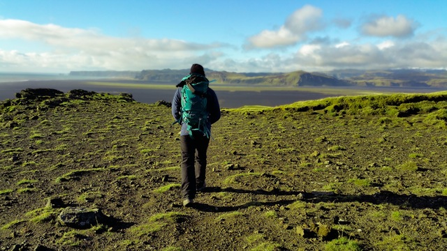 Man walking to a cliffs edge to overlook valley.