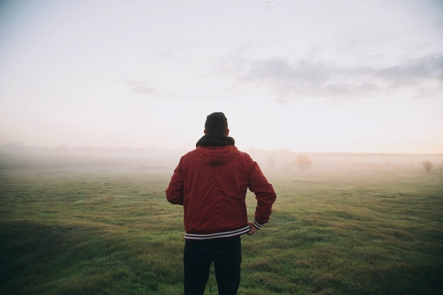 Man looking over a foggy field.