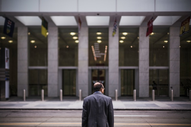 Man in a suit walking on a street looking at a building.