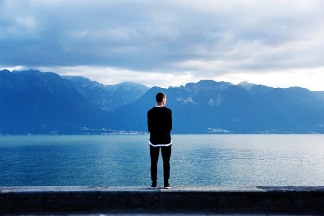 Man standing on a ledge overlooking a lake in the valley of mountains.