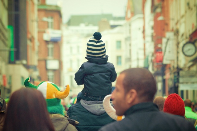 Child sitting on the shoulders of its father who is walking through a crowd.