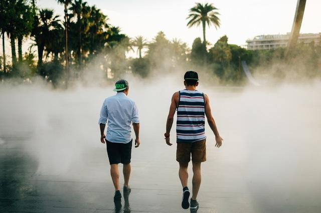Two men talking into a fog side by side.