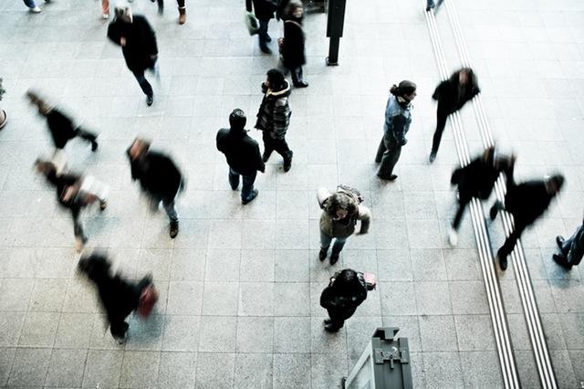 Crowd of people walking in a public area.