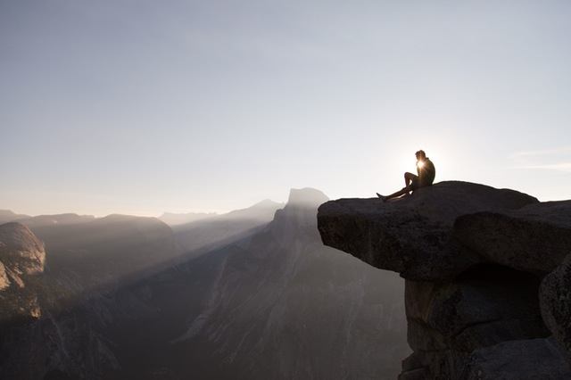 Man sitting on edge of cliff overlooking canyon.