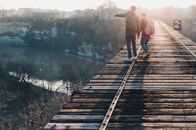Two men walking on a train trestle looking down a valley.