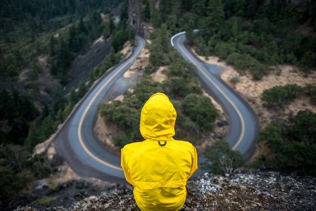 Man looking over a cliff observing a road.