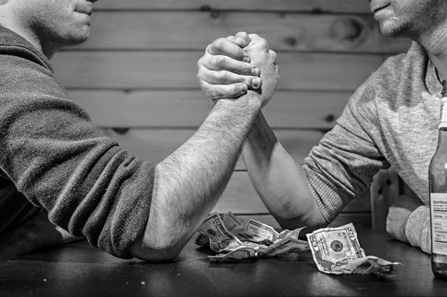Two men arm wrestling.