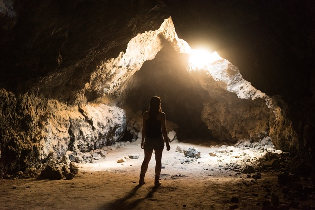 Woman standing in a cave looking at an opening.
