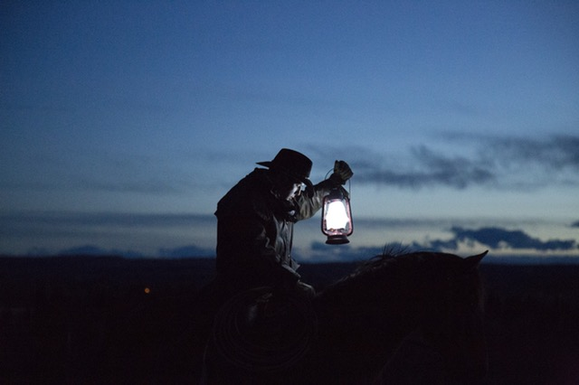 Man holding a lantern in a field.