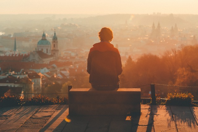 Man sitting on a box overlooking a city while the sun sets.