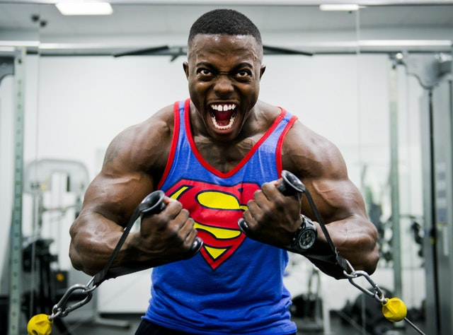 Man working out while wearing a superman shirt.