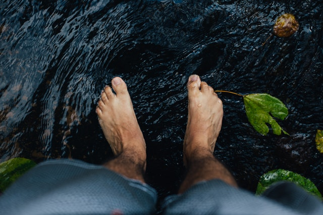 Feet standing in water.