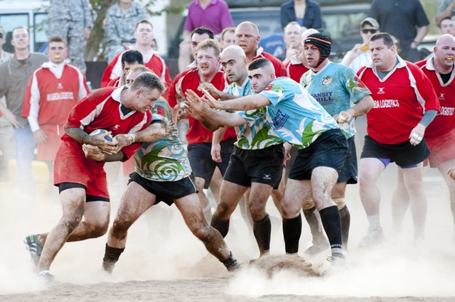 A group of men playing rugby and about to tackle a man.