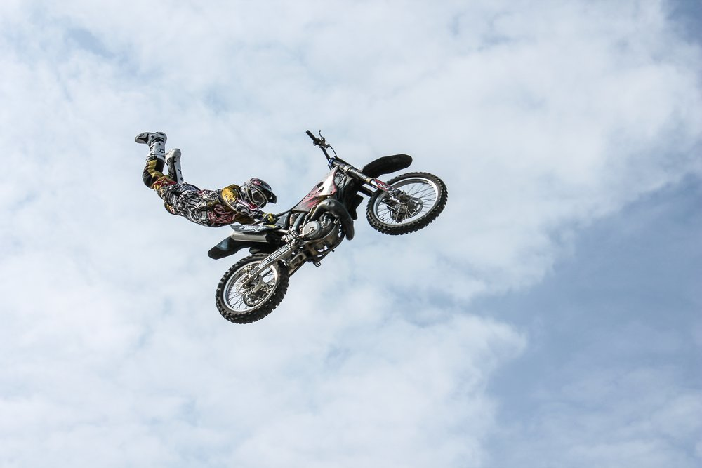 Man flying through the air holding a motorcycle.