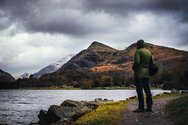Man standing on a path overlooking a lake in a valley.