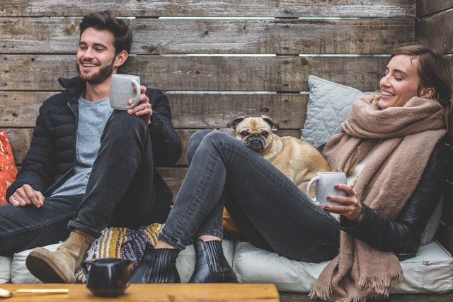 Man and woman sitting with mugs of coffee while a pug lays in the lap of the woman.