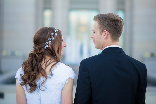 Man and woman wearing wedding clothes looking at each other.