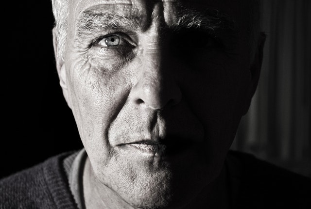 Old man starting intently with half his face dark.
