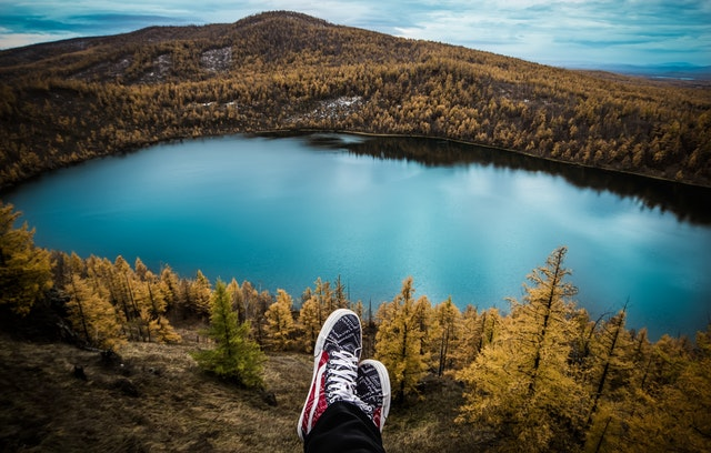 Man sitting with his feet showing while looking down at a lake in a valley.