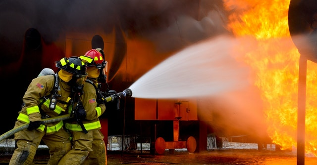 Two firefighting men holding a hose that is spraying water towards a fire.