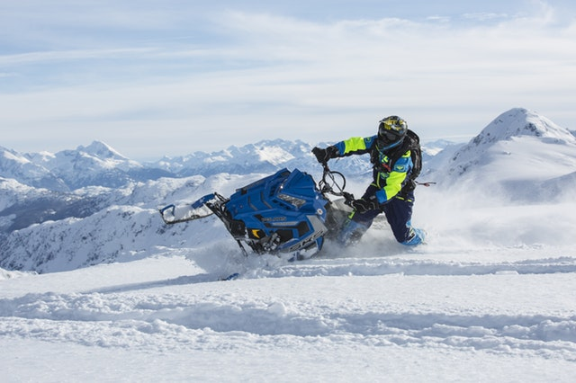 Man riding a snowmobile on a mountain top.