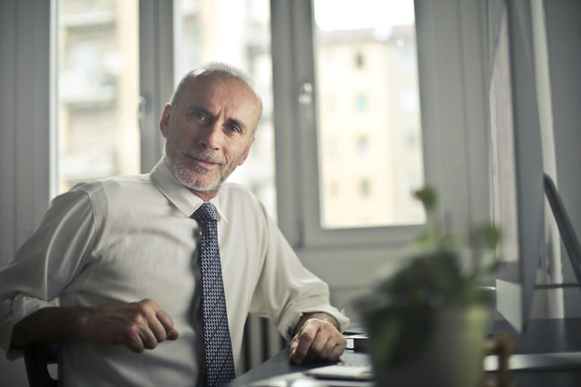 Older business man sitting at a desk.