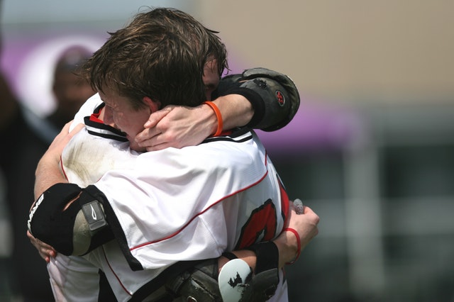 Two male lacrosse athletes hugging each other in happiness.