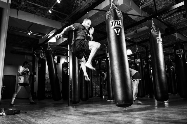 Confident man doing a flying kick at a punching bag.