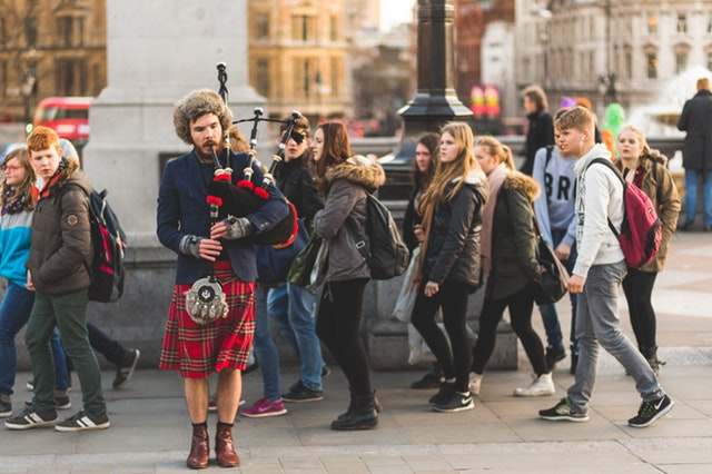 Confident man plays the bagpipes on the street.