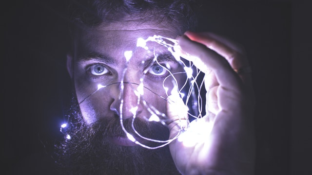 Masculine man holding lights up by his eyes while looking intently into the camera.
