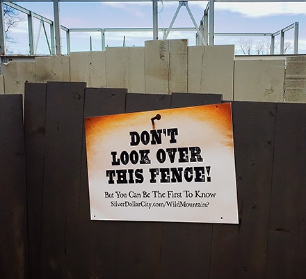 NO PEEKING?: A sign teases patrons of Silver Dollar City. Behind the fencing, the makings of a new ride are visible.
