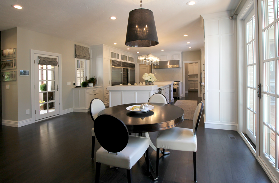 The kitchen is home to stunning features, including beautiful new lighting in the form of the dramatic chrome and glass island pendant, which is contrasted by the dark drum fixture hanging above the breakfast table.