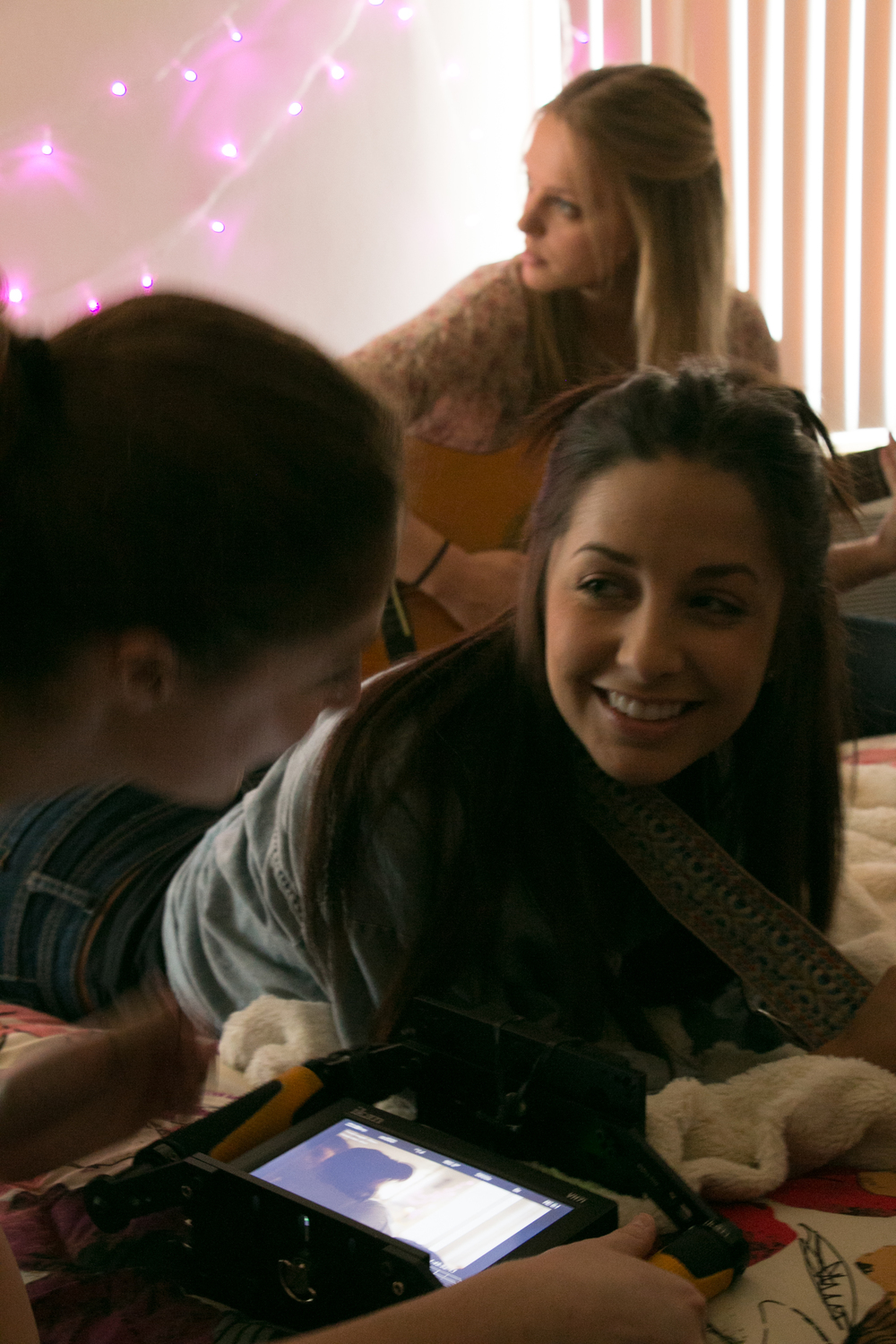 Jenna Michno practices guitar while Adriana Leonard laughs with director Dana Brawer