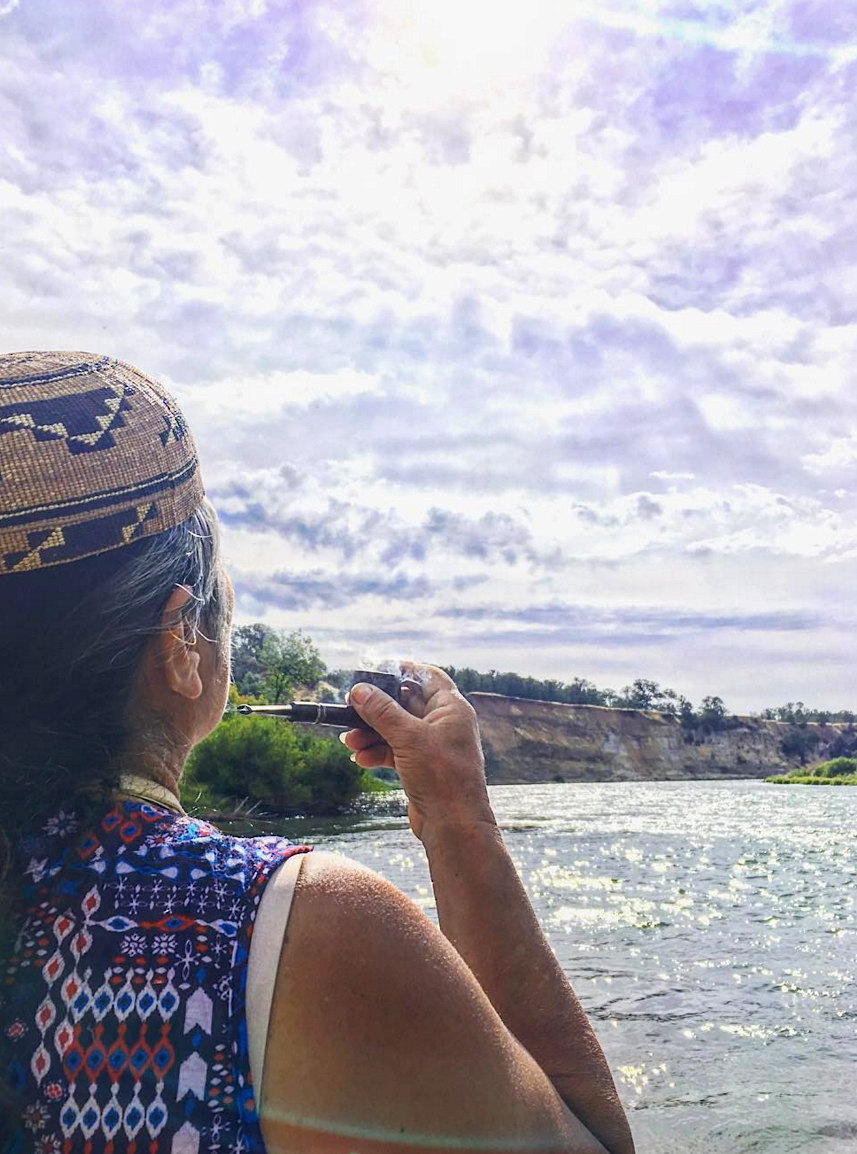 Caleen Sisk, Chief of the Winnemem Wintu, praying at Cow Creek on the Sacramento River, that the salmon may return home in a good way. Photo by Corrina Gould, founder of  Sogorea Te' Land Trust
