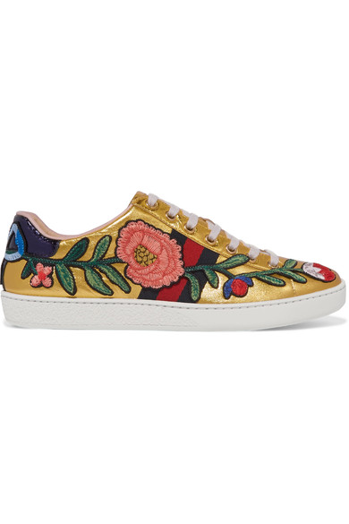GUCCI   Ace watersnake-trimmed appliquéd metallic leather sneakers £485  Alessandro Michele is surrounded by the color gold in his office - he works from Gucci's Renaissance headquarters in Rome with original architecture by Raphael. Part of the Resort '17 lineup, these leather 'Ace' sneakers feature the house's iconic navy and red striped webbing coordinated with watersnake heel tabs. The intricate floral and bow appliqués are recurring motifs in the collection.    https://www.net-a-porter.com/gb/en/product/800505/Gucci/ace-watersnake-trimmed-appliqued-metallic-leather-sneakers