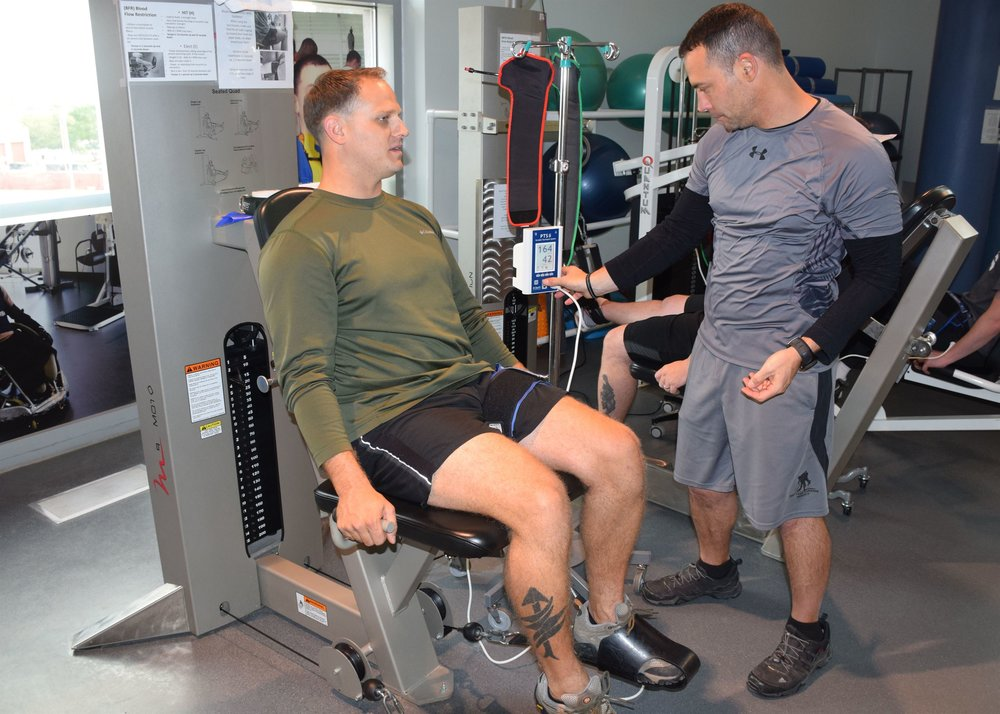 An example of BFR in action. Johnny Owens, chief of the Human Performance Optimization Program at the Center for the Intrepid's outpatient rehabilitation center, Brooke Army Medical Center, Texas, adjusts the pressure of a tourniquet, while Marine Corps Staff Sgt. Brandon Kothman performs leg extensions. Owens has successfully helped over 200 personnel rebuild muscle strength and function over the past two years, with the help of BFR.  U.S. Army photo  by Robert D'Angelo