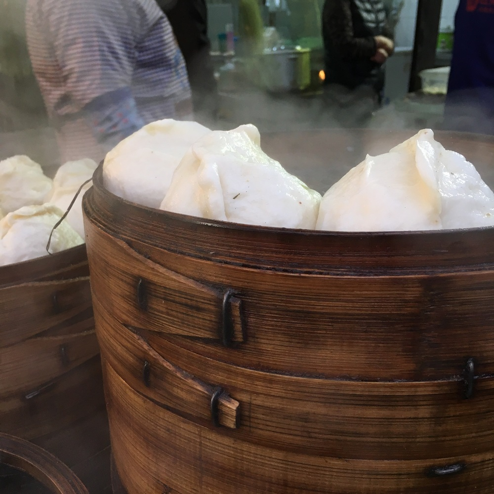 Some dumplings steaming in a food stall.