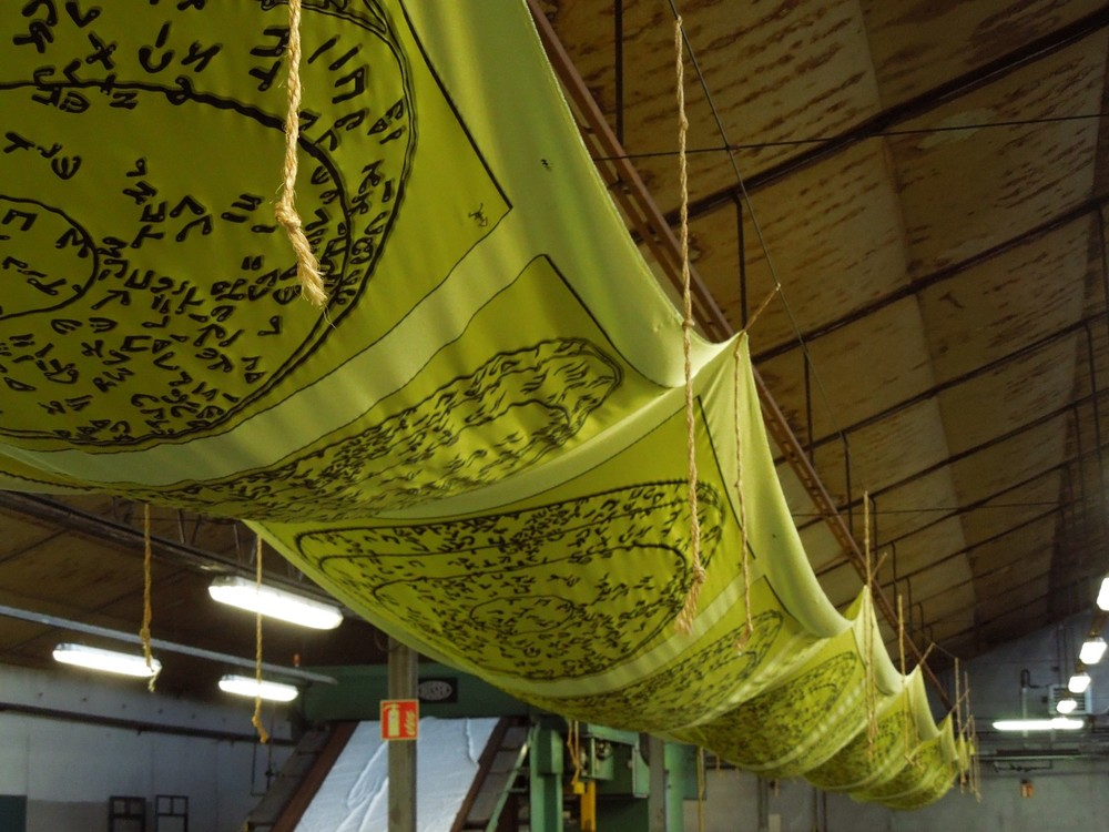 Freshly printed silk hanging to let the dye settle into the fabric .This helps the design to be clearly visible on the reverse which is the mark of a perfect print.