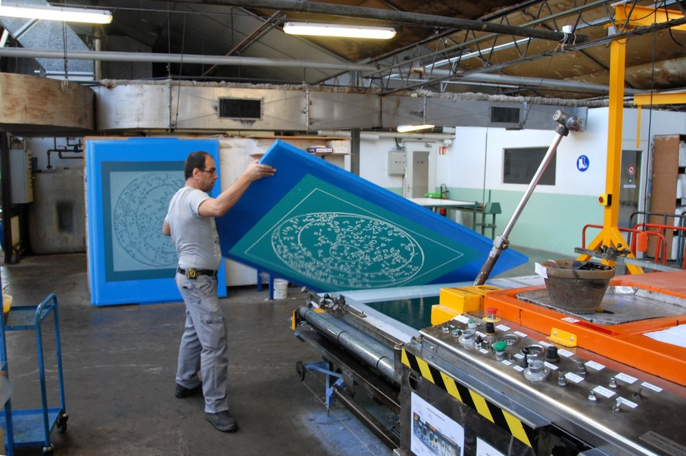 "Artisan printer laying a silk screen on the track for the traditional ""Impression à la Lyonnaise"" technique"