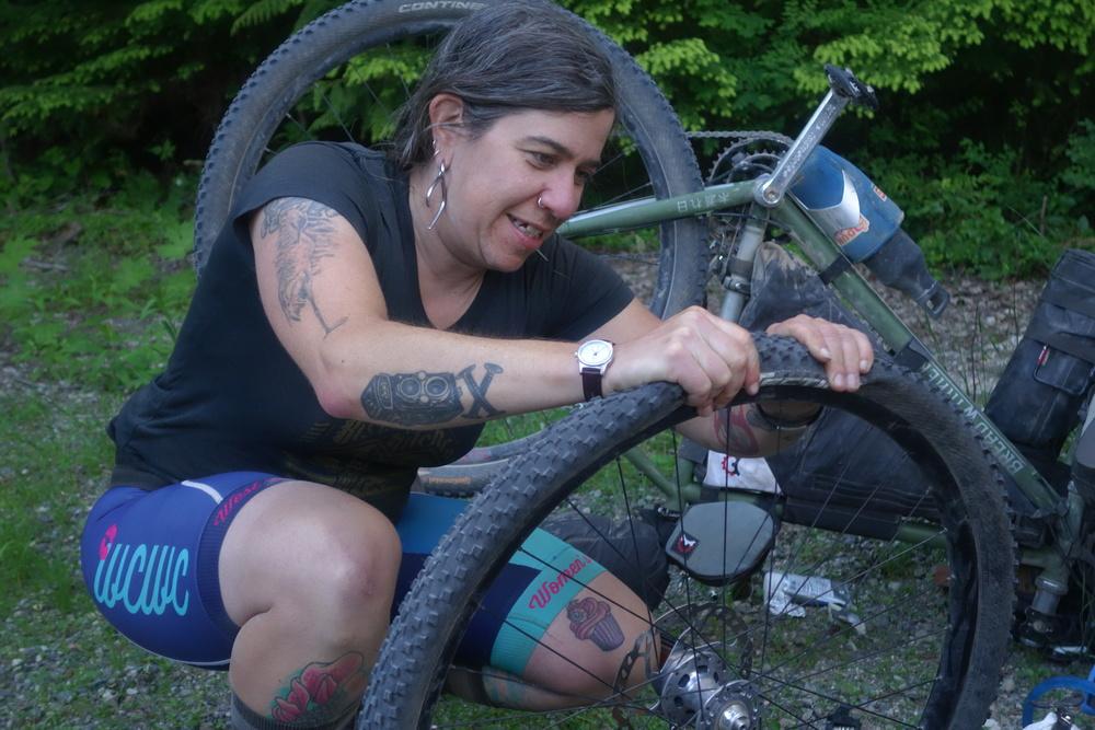 Hazel, Komorebi Cycling team pro mechanic, fixes a flat. Photo by Jocey.