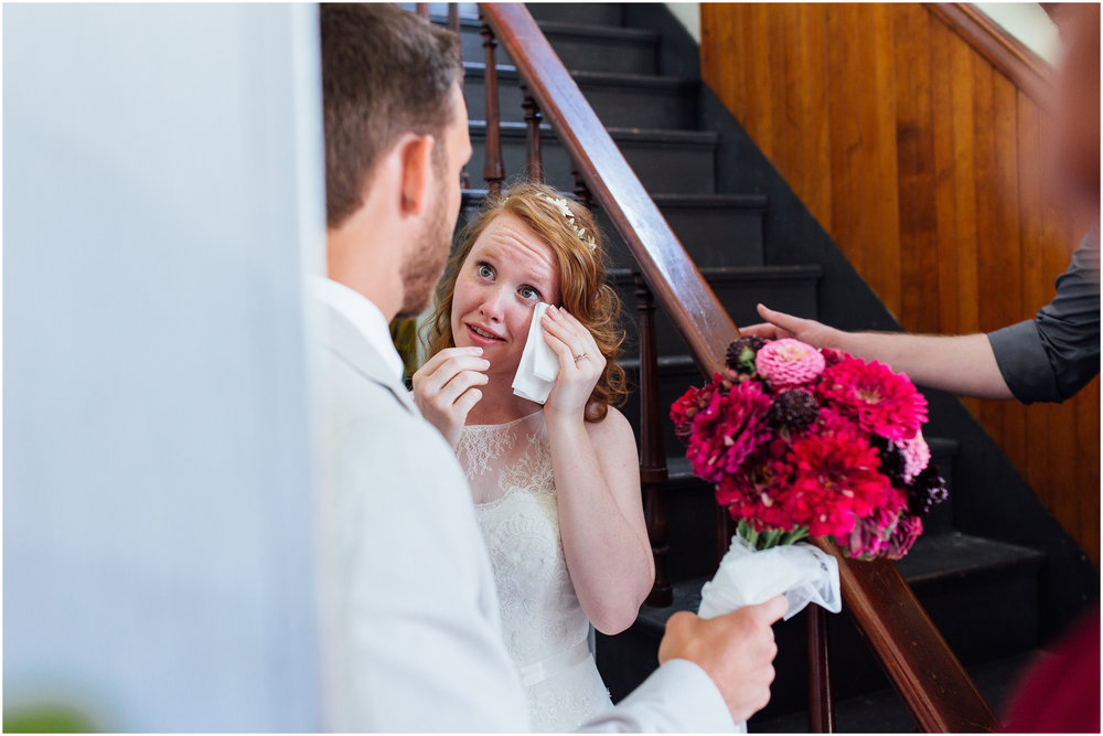 Bride wipes tear from her eye after wedding ceremony