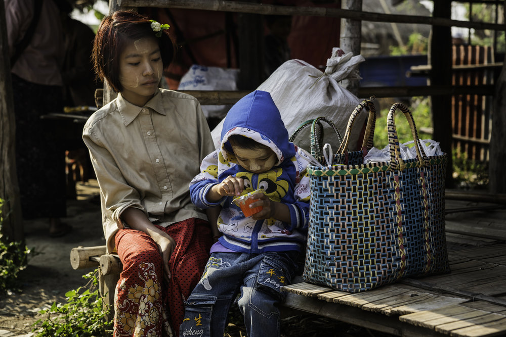 A girl and her little brother are waiting for the parents at the market.