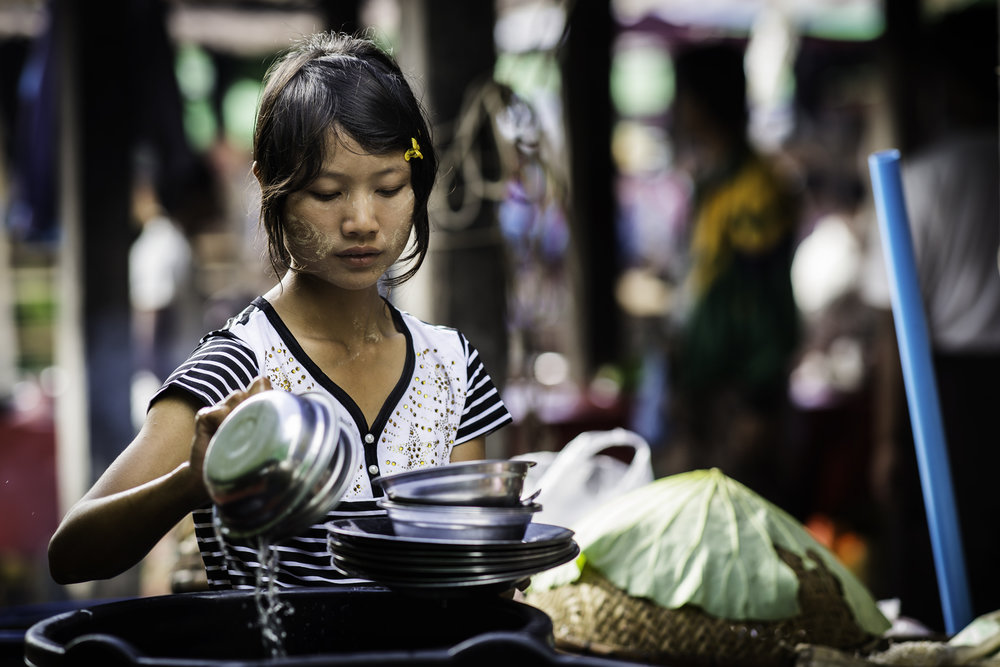 A girl is washing the dishes at the food stand at the market.